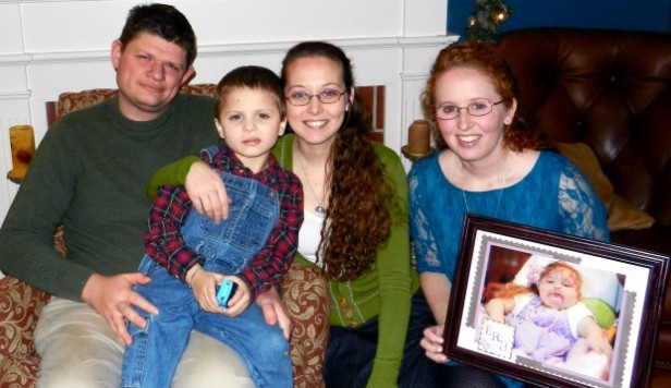 Sean and Jessica Hilliard sit with their son, Gabriel Hilliard, as Hilliard's sister, Jill Shriver, holds a picture of Eithene. (Photo credit: Jessica Hilliard)