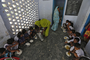 A cook serves the free mid-day meal, distributed by a government-run primary school, to children in Chapra district