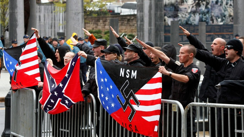"Members of the neo-Nazi National Socialist Movement hold flags as they salute and shout ""Sieg Heil"" during a rally in front of the Statehouse in Trenton, N.J., Saturday, April 16, 2011. (AP Photo/Mel Evans)"